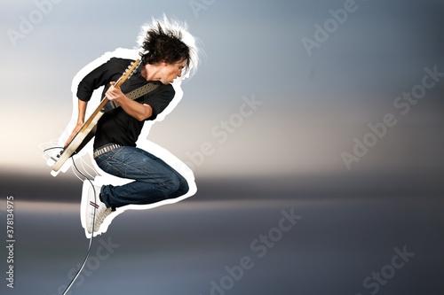 Fototapeta Male guitarist playing music on guitar and jump obraz