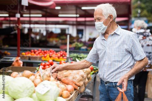 Fototapeta mature european man wearing medical mask protecting against the virus buying potatoes in market obraz
