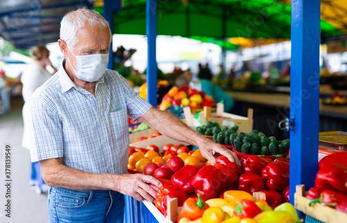 Fototapeta retired european man wearing medical mask protecting against virus buying tomatoes in market obraz