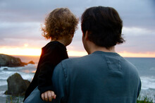 Back View Of A Father Holding His Toddler Girl As They Look At The Sunset Over A Rocky Pacific Northwest (USA) Beach