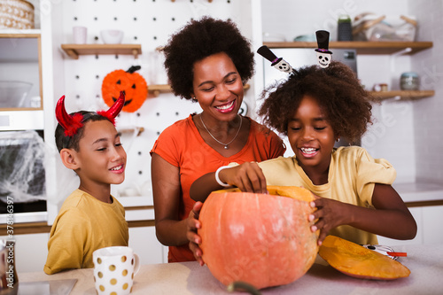 Photo Happy family mother and children prepare for Halloween