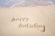 Happy Holiday Written In The Sand