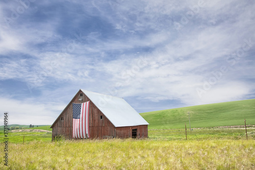 Obraz na plátně Original photograph of an old red barn with an American flag hung from the front