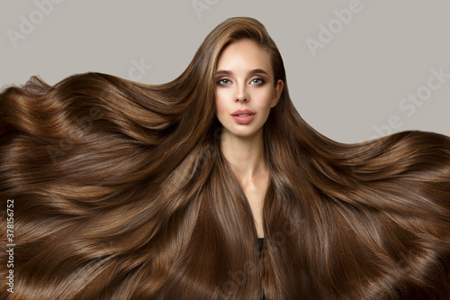 Foto Bright beautiful brunette woman with luxurious curly long hair