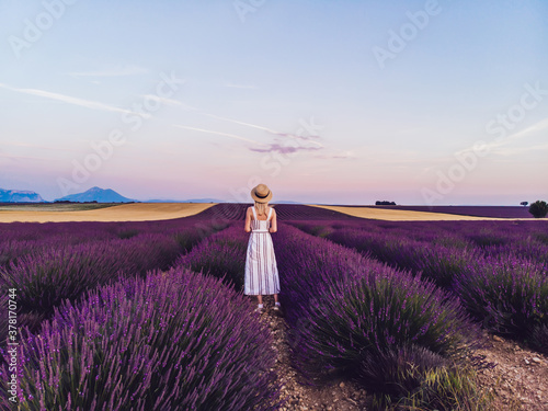 Anonymous woman in summer wear admiring landscape at lavender fields Wallpaper Mural