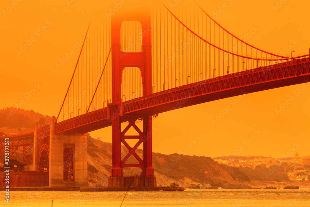 Fototapeta Bottom view of smoky orange sky on Golden Gate Bridge of San Francisco city from Lime point. California fires in September 2020 in United States. Wildfires composition.