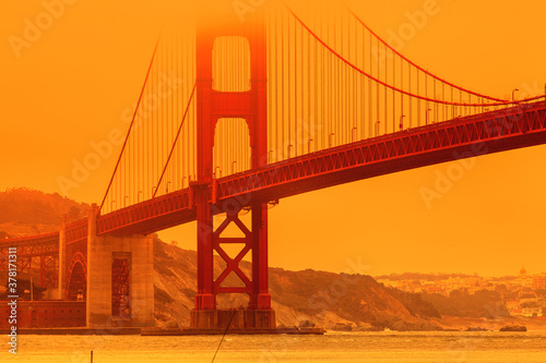 Fototapeta Bottom view of smoky orange sky on Golden Gate Bridge of San Francisco city from Lime point. California fires in September 2020 in United States. Wildfires composition. obraz
