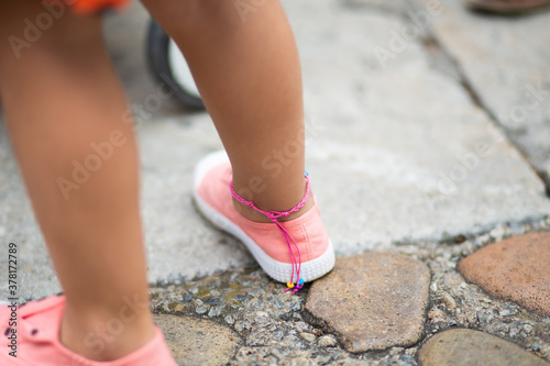 Fototapeta Pink leg bracelet on a baby girl wearing pink
