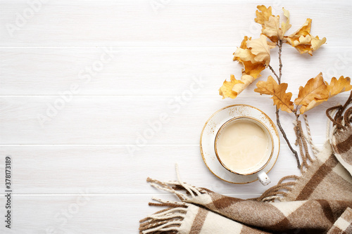 Warm woolen blanket and cup of hot drink on white wooden table. Cozy autumn concept