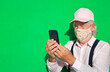 Leinwandbild Motiv Attractive senior man with pink cap wearing a fantasy medical mask due to covid-19 using smart phone app taking a selfie for friends - tech and social elderly people with green wall in background