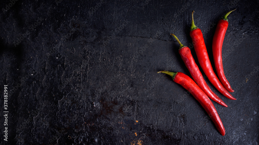 Fototapeta Red hot chili peppers on black rustic textured slate from above. Food background with spicy chilli paprika.