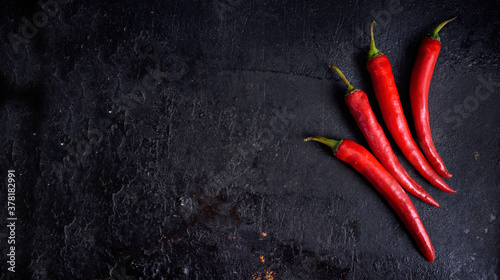 Foto Red hot chili peppers on black rustic textured slate from above
