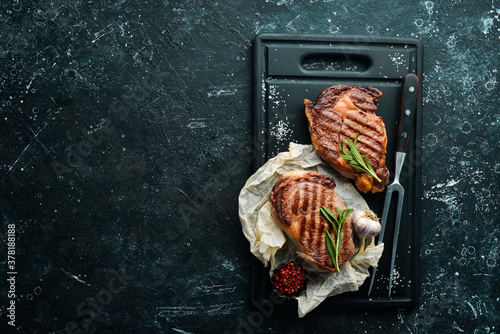 Fototapeta Grilled ribeye beef steak with spices on a black stone table. Top view. Free space for your text. obraz