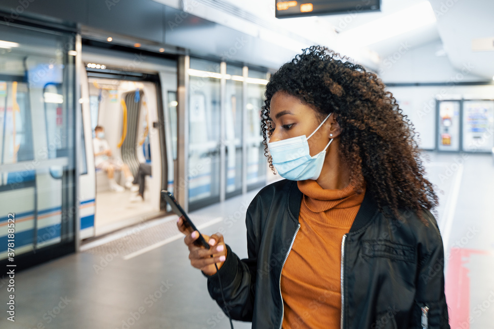 Fototapeta Afro woman wearing face mask in metro station