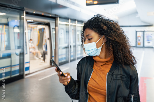 Fototapeta Afro woman wearing face mask in metro station obraz