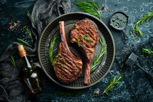 Juicy Steak Grilled On The Bone With Spices And Herbs. On A Black Stone Background. Top View. Free Copy Space.