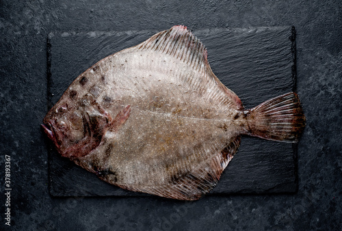 Cuadros en Lienzo raw flounder with spices on a stone background