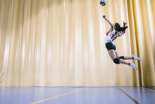 Professional Female Volleyball Player In Action Serving Ball In Madrid, Spain.