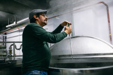 Brewer Adding Extract Into Beer Tank