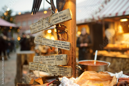 Foto Menu written in different languages on wooden plates on the most authentic Christmas market in Riga offering dozens of crafts and food stalls