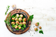 Baked Snails With Garlic Butter And Fresh Herbs On A Black Plate On A White Wooden Background. Top View. Free Space For Your Text.