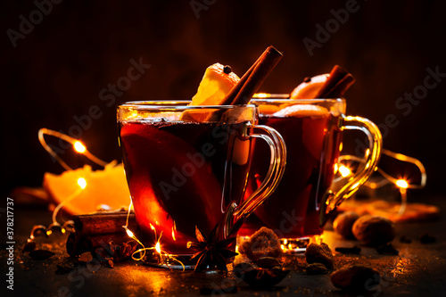 Fototapeta Christmas mulled red wine with spices and fruits on wooden rustic table. Traditional Christmas or New Year hot drink in festive light table setting obraz