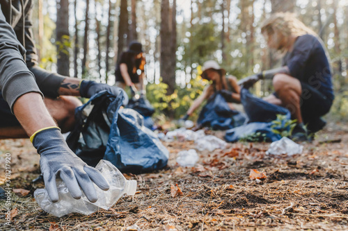 Close up of hands with plastic bottle with group of young people friends volunteers collecting plastic bottles to trash bags in forest background Canvas Print