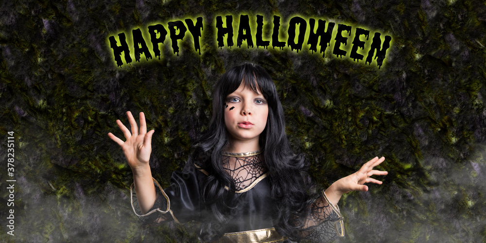 Fototapeta little girl in witch costume and message HAPPY HALLOWEEN in front of Halloween background
