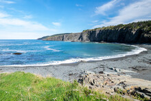 Bright Blue Ocean With A Small White Wave As It Meets The Empty Pebbled Beach In The Summer. There's A Cliff Surrounding The Cove With Trees And Grass On Top. The Sky Is Blue With White Clouds.