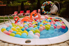 Beautifully Decorated Yard With Pool Balloons And Pink Flamingos. Garden Decoration For A Summer Party