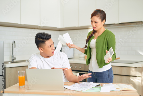 Fototapeta Young anxious couple quarrels by consulting their bank account obraz