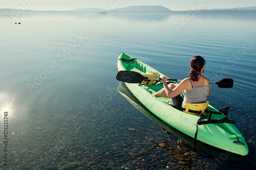 Valokuva Woman sitting alone in a green kayak waiting at the edge of the lake calm and tr