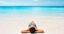 Beach Vacation Woman Lying Down Sun Tanning On Perfect White Beach Sand In Bikini Relaxing In Caribbean Island Destination. Girl Sunbathing During Summer Travel Holidays.