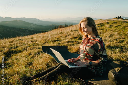 Girl working with laptop sitting in mountains. Hiker tourist enjoying valley view sunset. Vacation holidays in autumn day. Distant remote work and travel, freelance as lifestyle concept.