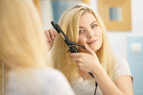 Fotografie, Tablou Woman using hair curler