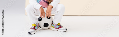 Fototapeta cropped view of girl in sportswear posing with soccer ball on beige and white background, panoramic shot obraz