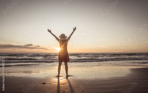 Obraz Woman in red with arms outstretched by the sea at sunrise enjoying freedom and life - fototapety do salonu
