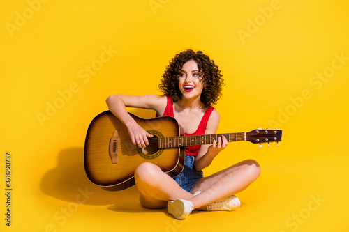 Obraz Portrait photo of hipster female musician with curly hair singing song holding keeping playing melody guitar chords smiling sitting down isolated on vivid yellow color background - fototapety do salonu