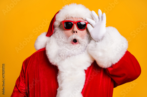 Close-up portrait of his he nice attractive amazed Santa father newyear celebration party pout lips touching specs bargain isolated over bright vivid shine vibrant yellow color background