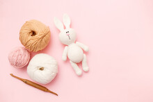 White And Brown Knitting Wool, Rabbit Amigurumi And Crochet Hook On Pink Pastel Background. Top View, Flat Lay, Copy Space