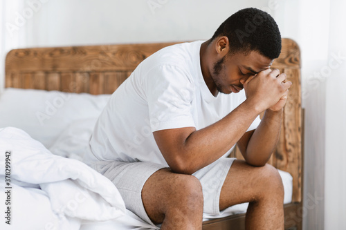 Vászonkép Depressed African Guy Having Insomnia Sitting On Bed At Home