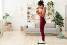 Joyful Black Woman Weighing Herself After Successful Weight Loss Indoors