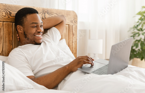 Cheerful African Man Using Laptop Watching Movie Lying In Bed Canvas Print