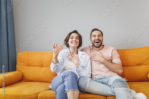 Fototapeta Laughing cheerful funny young couple two friends man woman 20s wearing casual clothes sitting on couch hugging spreading hands looking camera resting relaxing spending time in living room at home. obraz