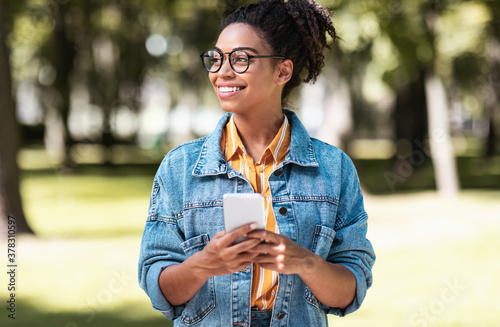 African Student Girl Using Cellphone Walking On Weekend In Park - 378310597