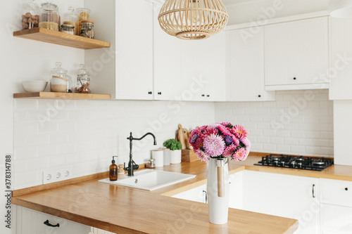 Fototapeta View on clean white simple modern kitchen in scandinavian style, aster Michaelmas daisy bouquet in vase on the table obraz