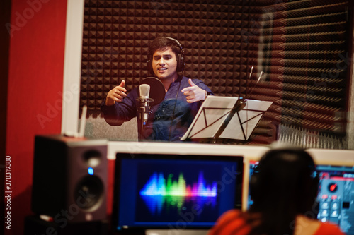 Photo Young asian singer man with microphone recording song in record music studio with sound producer