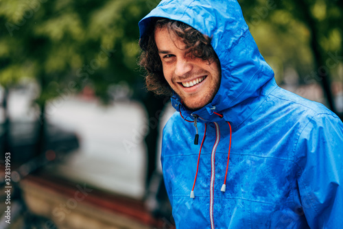Closeup portrait of a happy man smiling, wearing blue raincoat during the rain outside. Cheerful male enjoying the rain in the city street. The guy has joyful expression in rainy weather.