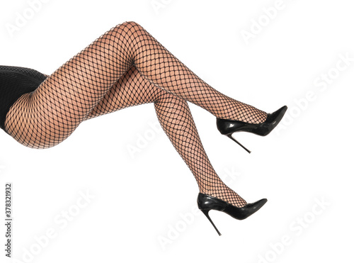Obraz pretty female legs in fishnet stockings and black high heels - fototapety do salonu