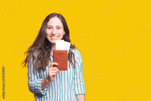 Foto smiling pretty woman looking confident at camera and showing passport with ticke